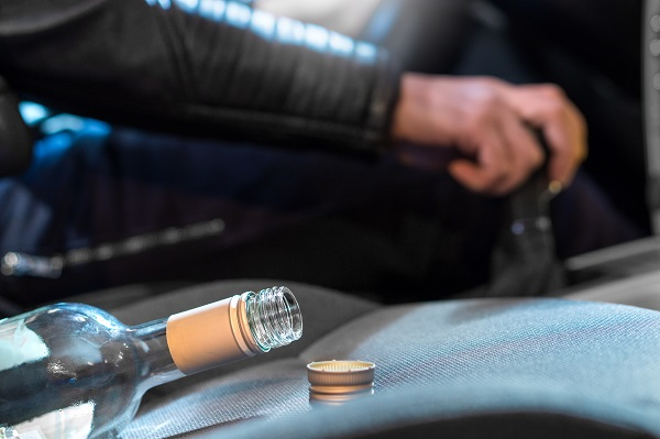 Drunk driver shifting gears with an empty wine bottle in the seat next to him