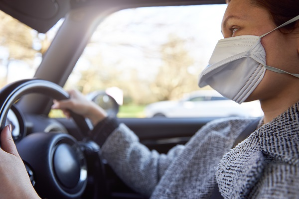 A woman wears a protective face mask while driving a car.